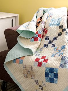 This vintage scrappy quilt features rows of nine-patch blocks on a white background. The nine-patch in this quilt were made from homemade shirts and dresses.