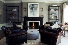 Living room. Leather chairs. Dark finish fireplace. White chair rail.