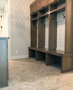 Mudroom with herringbone brick floor, lockers with shiplap and hooks, storage, gray walls, white trim