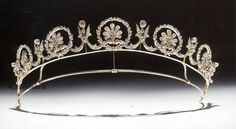 A diamond floral tiara, dating from 1890, made in Britain. Designed as a series of five laurel wreaths, with daisies inside, linked by foliate scrolls to spacers topped with circular diamonds.