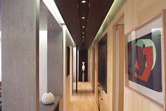Este es el pasillo. Es muy largo y tiene muchas puertas. Hay algunas imagenes y un florero.