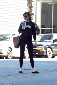 In shape: The Fifty Shades star looked fit in skin-tight black leggings, a black sweater, and black slides