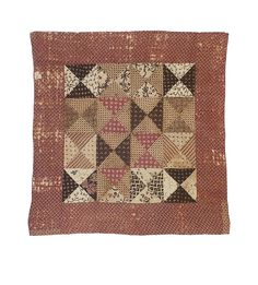 """Pieced cradle quilt with side by side blocks made of four triangles each, pattern known as """"broken dishes""""; border of predominantly red printed cotton, patched with wool; hand quilted."""