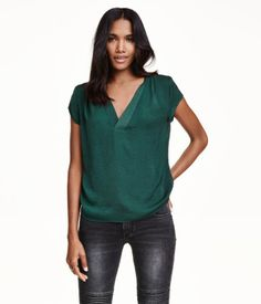 Short-sleeved, V-neck blouse in satin with pleats on shoulders and at back of neck. Rounded hem, slightly longer at back.