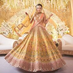 the stunning dons this handcrafted Lehenga in yellow and peach. Motifs of fresh blossoms are scattered on this luxurious silk Lehenga with fine crafts of Rajasthan. Designer Bridal Lehenga, Indian Bridal Lehenga, Indian Bridal Outfits, Indian Dresses, Bridal Dresses, Wedding Lehnga, Wedding Outfits, Mehendi Outfits, Bridal Sarees