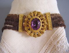 "GEORGIAN/early VICTORIAN rare pinchbeck and woven hair bracelet with a faceted purple paste stone in a cannetille work clasp. Four colors of plaited hair made up this bracelet, which makes me wonder if it might have been made by four daughters for their mother. It is 7"" long and 1-1/4"" wide."