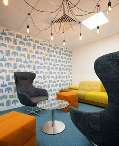 Meeting Rooms > Cool Meeting Spaces > This meeting room is a clear break from the corporate mould! The cool wallpaper has a retro computer print with images of the Nintendo GameBoy plus other retro Sega and Nintendo joypads and joysticks. Colourful seating including a yellow sofa and orange pouffes add bright contrast against the blue carpets. The unusual chandelier is actually made up of a series of exposed lightbulbs draped around the ceiling. See more office design inspiration on our…