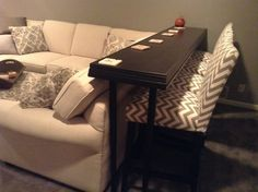 Bar behind sofa to allow more seating. Works perfect in the basement family room. Table top is black hardwood flooring trimmed with crown molding. I bought adjustable legs at IKEA and painted them black.