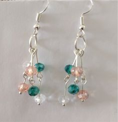 Charming chandelier earrings handcrafted with stainless steel and pastel faceted glass beads in crystal, vintage rose, and emerald glass beads.