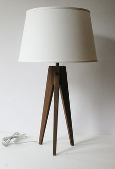 Please Note: This lamp is made to order. Please allow 10 to 14 days before shipping. Shades are sold separately. Brighten up your home or office with the new tripod Slim table lamp! The Slim provides an alternative design to my original tripod lamp line, by providing a more slender appeal for those smaller spaces. The Slim features a unique three-sided tapered leg giving it a clean and graceful look from any angle. The cord has been concealed in routed groove on the interior side of one leg…