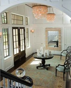 Entry perfection!  Classic white millwork, Capiz shell chandeliers, French doors with sidelights and transoms, round table, crystal finial on stairs! Via http://hookedonhouses.net/
