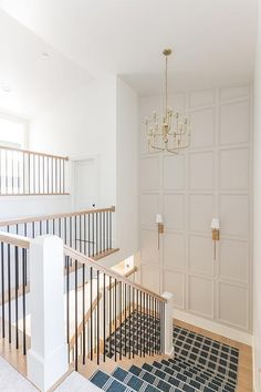 Staircase landing wall features light gray trim and brass sconces illuminating t. Staircase landing wall features light gray trim and brass sconces illuminating the stairs. Stairs Feature Wall, Stairwell Wall, Stairway Walls, Staircase Wall Decor, Staircase Runner, Staircase Design, Runners For Stairs, Dining Room Feature Wall, Foyer Staircase