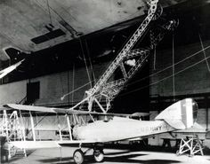 Vought UO-1 (Bu# A-6615) attached to the trapeze of USS Los Angeles (ZR 3) during mating experiments in the airship hangar at NAS Lakehurst, New Jersey, 15 December 1928.