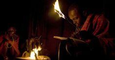 Estudante faz lição de casa, com apoio da luz do fogo, no município de Kisima, em Samburu, no Quênia. Ele faz parte de um projeto de aulas noturnas, ministradas por professores voluntários, para trabalhadores do campo que normalmente não conseguem frequentar a escola durante o dia