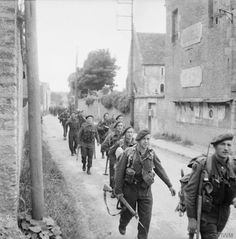 Royal Marine Commandos attached to 3rd Division for the assault on Sword Beach move through Colleville-sur-Orne on their way to relieve forces at Pegasus Bridge, Normandy, 6 June 1944. © IWM (B 5067)