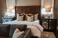 Earth-tone clad contemporary bedroom features a brown velvet tufted wingback headboard supporting a bed dressed…