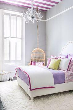 Modern White girls bedroom: white upholstered bed, pink purple bedlinen, shag rug, cane rattan hanging egg chair, glass chandelier