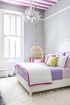 Modern White girls bedroom: white upholstered bed, pink purple bedlinen, shag rug, cane rattan hanging egg chair, glass chandelier