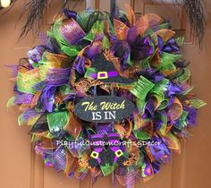 The Witch Is In Halloween Wreath is gorgeous and shimmers when the light hits it. The wreath has all the halloween colors, glitter polka dot ribbon, spider ribbon, and bat ribbon. It also has a wooden