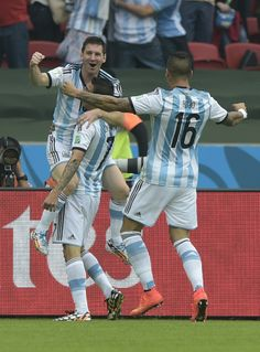 Let Lionel Messi Show You What A Perfect Free Kick Goal Looks Like - Argentina's forward Lionel Messi (L) celebrates his goal with midfielder Angel Di Maria (C) and defender Marcos Rojo, during a Group F football match between Nigeria and Argentina at the Beira-Rio Stadium in Porto Alegre during the 2014 FIFA World Cup on June 25, 2014.