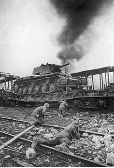 German Army soldiers advance through a Red Army depot with KV-1 tanks still on delivery trains.  Smolensk, Russia, 1941