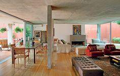 A sala incorporou a garagem na reforma do arquiteto André Vainer. Hoje o living é amplo e integrado por portas de vidro deslizantes com a varanda