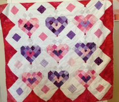 This one was made from leftovers of Little Miss' pink and purple quilt. I took buttons and tied them to the center of each heart.