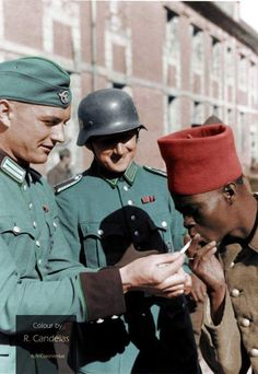 Two members of the German Schutzpolizei light a French colonial soldier's cigarette. France, May/June 1940. With the outbreak of war, the German 'Ordnungspolizei' formed a considerable number of rifle...