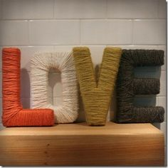 Cardboard letters wrapped in yarn, cute...Kids names would be cute too