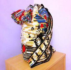 Nefertiti bag was mainly made in tapestry crochet with shaded yarn. Patterns feature head of egyptian queen Nefertiti, winged sun, eye of Horus and hieroglyphs.  Dimensions: Height 45cm, diameter: 25cm. Strap adjustable, decorated with text NEFERTITI. Interior made of 3 layers of quilted fabric (2x cotton, 1x satin) - give feeling of softness and luxury. Additionally inside: small pocket closed with a zipper and decorated with crochet. The bag is closed with thick cord with pompons.