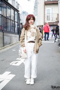 Meet Conomi, a 22-year-old girl. She is wearing a resale jacket (Claude Cross) and ruffle blouse with white pants from the Japanese brand Tomorrowland. Her tote bag is Today's Special and her white canvas sneakers are H&M. She is also wearing a Celine headscarf, stud earrings, and thin rings. She likes to buy her clothes from resale shops and that she listens to Maximum the Hormone.