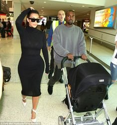 Quick fix: The 33-year-old was seen fixing her neat ponytail as Kanye took care of pushing little North around in her stroller