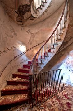 """A spiral staircase in a decrepit hotel in """"Paper City."""""""