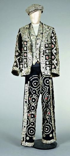 Circa 1910 Pearly King ensemble of pants, a heavy tweed jacket, waistcoat, and cap smothered in mother-of-pearl buttons.  The practice of wearing these outfits was started by Henry Croft to draw attention to himself and aid in his fund-raising activities. Pearly Clubs have formed all over London. Each group is associated with a church in central London and is committed to raising money for London-based charities.  Woman members are known as Pearly Queens.