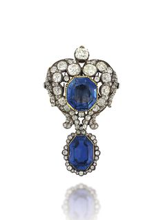 AN EARLY 19TH CENTURY SAPPHIRE AND DIAMOND BROOCH -  The central octagonal-cut sapphire collet-set to an old-cut diamond heart shaped scrolling border, suspending a detachable similarly-set sapphire and diamond drop, mounted in silver and gold.