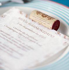 O menu é exposto sobre o prato de cada convidado, preso por uma rolha.