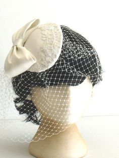 Graceful Bride - Custom made Ivory white satin bow and lace cocktail hat. French birdcage wedding veil. Handmade by Bettina Millinery.
