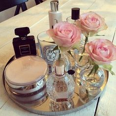 Mirrored tray with perfume, moisturiser and some roses on my dressing table