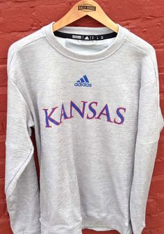 Make a sporty statement with this Kansas Jayhawks Adidas Mens Grey Locker Official Font Sweatshirt! Rally House has a great selection of new and exclusive Kansas Jayhawks t-shirts, hats, gifts and apparel, in-store and online. Kansas Jayhawks Basketball, Kentucky Basketball, Duke Basketball, Basketball Players, College Basketball, University Of Kentucky, Kentucky Wildcats, Team Names, Texas Rangers