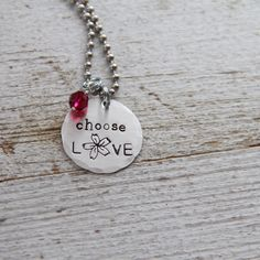 """**Until May 1, $10 from each of these necklaces will go directly to the Martin Richard family fund, victims of the Boston bombings.**A sterling silver disc is hand stamped with the words Choose Love, including our exclusive pretty flower. Each letter is individually stamped into the metal, so your piece will be completely custom to you! This is strung on an 18"""" stainless steel ball chain and measures just under 1"""" in diameter.  It's paired with a Ruby colored S..."""