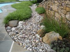 Dry stream bed.  Water only flows through this during heavy rains.  An ornamental way of directing storm water off your property!  Boulders and and plantings make it look natural.