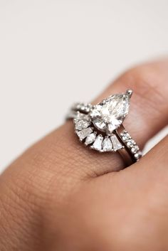 A fan of marquise, tapered baguettes and pear cut diamonds to arch around a center stone and enhance its sparkle. With modern and romantic vibes, she is the ultimate addition to any bridal stack.