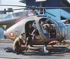 """OH-6 """"Loach"""" crew Tim Brennan, Hugh Mills and Mike King idling at a Can Tho AAF revetment in Vietnam, 1972"""