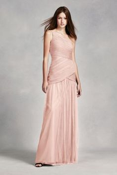 This artfully ruched bobbin net long bridesmaid dress starts with a one-shoulder illusion neckline and finishes with a floor-length skirt.  Illusion one shoulder dress features ruching throughout bodice.  Dropped waist