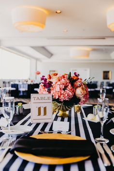 Black, White, and Gold Wedding Reception Table Decor with Elegant Printed Table Number Card, Low Tropical Floral Centerpiece in Round Gold Vase, and Striped Table Runner | Private Tampa Bay Wedding Venue The Centre Club