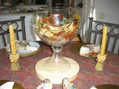 Thanksgiving candle w/mini pine cones, fall leaves (both from Crate and Barrel) & fish bowl vase (from Z Gallery). Put a glass cylinder vase in middle of fish bowl vase and put candle inside to protect it from burning the leaves.