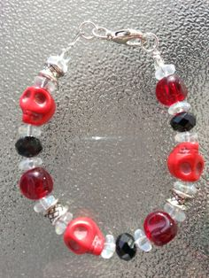 This is a 7 1/2 inch bracelet that can be made in to any size. Just message me. It is made of red stone skulls, silver metal beads, black, ruby and clear glass beads. It has a silver metal lobster claw clasp.