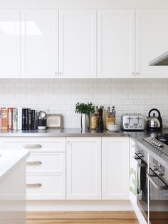 La cocina sencilla blanca está alicatada con baldosas tipo metro.