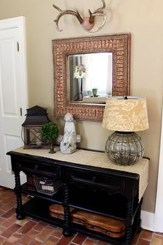 love the decorations on this entry way table.. minus that wear animal head.. yikess!