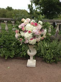 Tall Urns with rounded arrangement of hydrangeas, roses, lilies and foliages for ceremony or reception markers.
